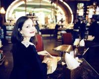 Mujer morena elegante joven en el café de consumición del café, lujo internacional Foto de archivo