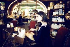 Mujer morena elegante joven en la consumición del café Foto de archivo