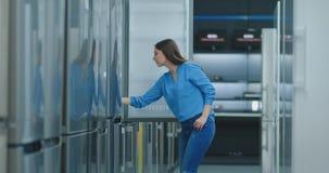 Mujer morena en la camisa para abrir la puerta del refrigerador en la tienda de dispositivos y a comparar con otros modelos a almacen de metraje de vídeo