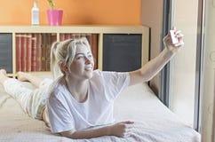 Mujer morena en su cama que toma el selfie en su teléfono foto de archivo libre de regalías
