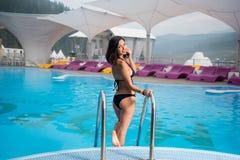 Mujer morena en un bikini del negro sexy cerca de la piscina y torneado de nuevo a sonrisa en la cámara en centro turístico de mo fotos de archivo libres de regalías