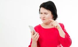 Mujer morena enojada en el glóbulo rojo de tenencia del vestido enfadado no trabajando el smartphone, muchacha adolescente furios imagenes de archivo