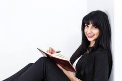Mujer morena feliz hermosa joven que sostiene un cuaderno vestido en un traje de negocios negro que se sienta en un piso en una o imagenes de archivo