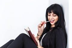Mujer morena feliz hermosa joven que sostiene un cuaderno vestido en un traje de negocios negro que se sienta en un piso en una o imágenes de archivo libres de regalías