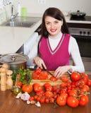 Mujer morena feliz que corta los tomates Fotografía de archivo