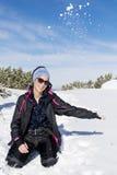 Mujer morena feliz que juega con una nieve en la montaña, gozando de la nieve del invierno Imagen de archivo