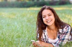 Mujer morena feliz que miente en hierba en parque con smartphone Imagen de archivo libre de regalías