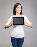 Mujer morena feliz que sostiene una tableta Foto de archivo libre de regalías