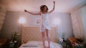 Mujer morena fresca feliz en el vestido de la noche que salta en la cama blanca por mañana y la sonrisa Hembra en humor alegre almacen de video