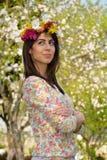 Mujer morena hermosa con la guirnalda de la flor en el jardín de la primavera Imágenes de archivo libres de regalías