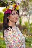 Mujer morena hermosa con la guirnalda de la flor en el jardín de la primavera Fotografía de archivo