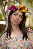 Mujer morena hermosa con la guirnalda de la flor en el jardín de la primavera Fotos de archivo libres de regalías