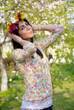 Mujer morena hermosa con la guirnalda de la flor en el jardín de la primavera Fotos de archivo