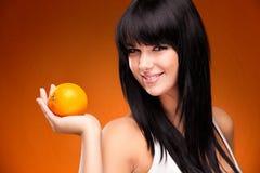 Mujer morena hermosa con la naranja en fondo anaranjado Fotografía de archivo