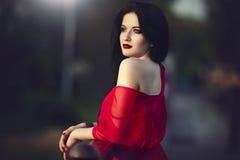Mujer morena hermosa con los labios y el vestido rojos Fotografía de archivo libre de regalías