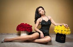 Mujer morena hermosa con los ramos de muchas rosas rojas y amarillas en el apartamento interior, día de tarjetas del día de San V imagen de archivo
