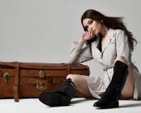 Mujer morena hermosa del inconformista en la chaqueta gris del otoño que miente en el bolso retro marrón de cuero del viaje en gr fotografía de archivo