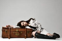 Mujer morena hermosa del inconformista en la chaqueta gris del otoño que miente en el bolso retro marrón de cuero del viaje en gr imagen de archivo libre de regalías