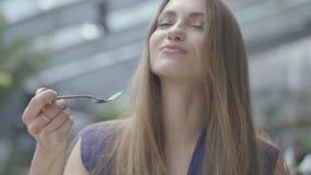 Mujer morena hermosa del retrato que come la torta con macarrones en el cierre del restaurante para arriba Se?ora caliente con he almacen de metraje de vídeo
