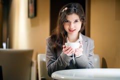 Mujer morena hermosa en café de consumición del restaurante Foto de archivo