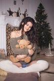Mujer morena hermosa en pantalones cortos y suéter en la decoración del Año Nuevo Fotografía de archivo libre de regalías