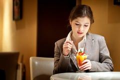 Mujer morena hermosa en restaurante que come el helado con las frutas Fotos de archivo libres de regalías