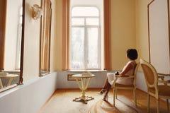 mujer morena hermosa en un vestido blanco que presenta cerca de la ventana imagen de archivo libre de regalías