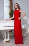 Mujer morena hermosa en un vestido rojo Tiro del estudio Pelo largo Labios rojos Imagen de archivo