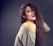 Mujer morena hermosa feliz con estilo de pelo largo en molestia gris Foto de archivo