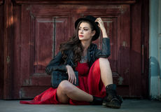 Mujer morena hermosa joven con la presentación del vestido del cortocircuito del rojo y del sombrero negro sensual en paisaje del Fotos de archivo