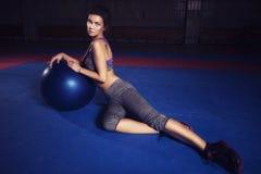 Mujer morena hermosa joven delgada apta con el fitball en sportswe imagenes de archivo