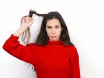 Mujer morena hermosa joven en el suéter rojo que juega con el pelo que muestra las emociones que presentan contra el fondo blanco Imagenes de archivo