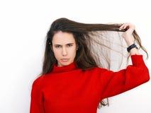 Mujer morena hermosa joven en el suéter rojo que muestra la emoción sospechosa que presenta contra el fondo blanco Imagen de archivo