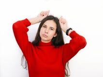 Mujer morena hermosa joven en el suéter rojo que muestra los cuernos con sus fingeres que presentan contra el fondo blanco Fotos de archivo