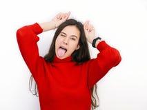 Mujer morena hermosa joven en el suéter rojo que muestra los cuernos con sus fingeres que presentan contra el fondo blanco Imagenes de archivo