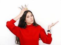 Mujer morena hermosa joven en suéter rojo y la corona diy que juegan a la princesa contra el fondo blanco Foto de archivo libre de regalías