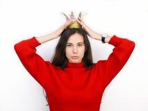 Mujer morena hermosa joven en suéter rojo y la corona diy que juegan a la princesa contra el fondo blanco Imagen de archivo libre de regalías