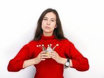 Mujer morena hermosa joven en suéter rojo y la corona diy que juegan a la princesa contra el fondo blanco Imagenes de archivo