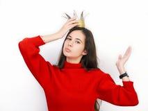 Mujer morena hermosa joven en suéter rojo y la corona diy que juegan a la princesa contra el fondo blanco Fotografía de archivo libre de regalías