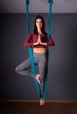 Mujer morena hermosa joven que hace yoga de la mosca El sentarse en hammoc Fotos de archivo