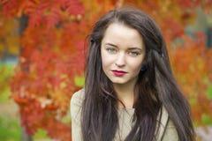 Mujer morena hermosa joven que presenta al aire libre en parque del otoño Fotografía de archivo libre de regalías