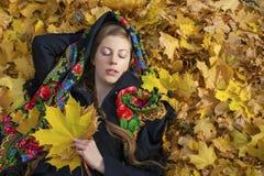 Mujer morena hermosa joven que presenta al aire libre en parque del otoño Fotos de archivo libres de regalías