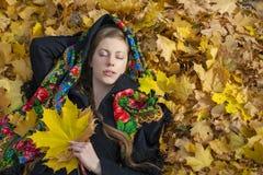 Mujer morena hermosa joven que presenta al aire libre en parque del otoño Foto de archivo libre de regalías