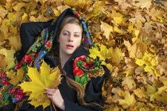 Mujer morena hermosa joven que presenta al aire libre en parque del otoño Imágenes de archivo libres de regalías