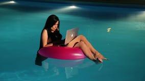 Mujer morena hermosa joven que trabaja en el ordenador portátil en la piscina almacen de video