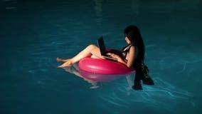 Mujer morena hermosa joven que trabaja en el ordenador portátil en la piscina