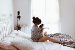 Mujer morena hermosa que acaricia su perrito de Labrador en dormitorio imagen de archivo