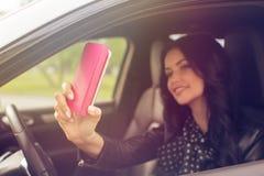 Mujer morena hermosa que hace el selfie en el coche Fotos de archivo