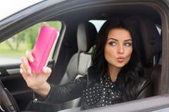 Mujer morena hermosa que hace el selfie en el coche Foto de archivo