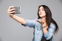 Mujer morena hermosa que hace un selfie que sopla un beso que celebra el smartphone aislado en un fondo gris foto de archivo